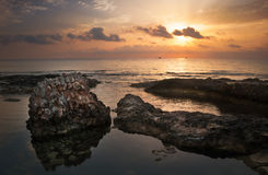 Sunset over the Sea and Rocky Coast with Ancient Ruins Royalty Free Stock Images