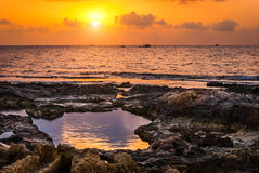 Sunset over the sea and rocky coast Stock Photo