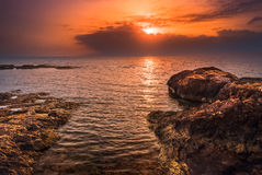 Sunset over the Sea and Rocky Coast Stock Photography