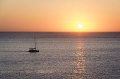 Sunset over sea with a sailboat. Mediterranean sunset and a sailboat in Ibiza island Royalty Free Stock Images