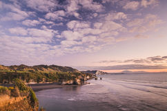Sunset over sea shore rocks and mount Taranaki, New Zealand Royalty Free Stock Photo