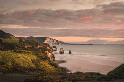 Sunset over sea shore rocks and mount Taranaki, New Zealand Royalty Free Stock Images