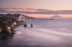 Sunset over sea shore rocks and mount Taranaki, New Zealand Stock Images