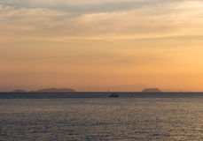 Sunset over the sea with small boat on the horizon Royalty Free Stock Images