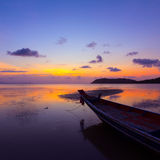 Sunset over sea with small wooden boat Stock Images