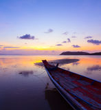 Sunset over sea with small wooden boat Royalty Free Stock Images