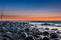 Sunset over the sea. Stones and fishing rods on the foreground Royalty Free Stock Photography
