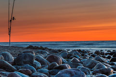 Sunset over the sea. Stones and fishing rods on the foreground royalty free stock photos