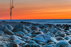 Sunset over the sea. Stones and fishing rods on the foreground Royalty Free Stock Images