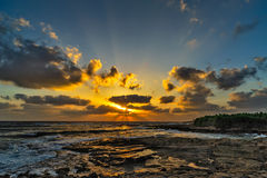 Sunset over the sea and stony coast Stock Image