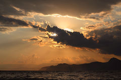 Sunset over the sea in summer. Against the backdrop of the mountains like a dragon Stock Image