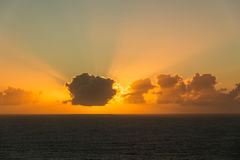 Sunset over the sea with the sun behind the clouds Stock Image