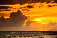 Sunset over sea surface, dark clouds. Stock Image