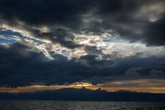 Sunset over the sea. Thunderclouds royalty free stock photography