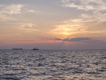 A sunset over the sea with two silhouettes of ships stock photo