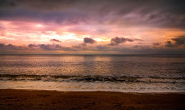 Sunset Over the Sea. View of a bright pink and orange cloudy sunset, viewed from the beach and shoreline, over a calm sea Royalty Free Stock Photo