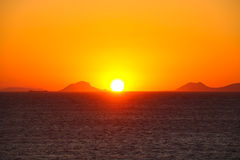 Sunset over sea water. Beautiful sunset over sea water and mountains silhouettes Royalty Free Stock Image
