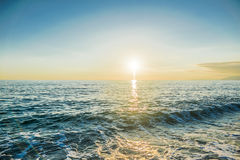 Sunset over the sea waves. Clear sky Stock Photos