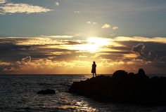 Sunset over the sea woman fishing Stock Photos