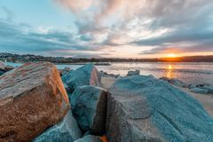 Sunset over shallow waters with huge boulders. Sunset over shallow waters with huge boulders stock photos