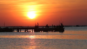 Sunset over shore of sea and fishing pier stock video