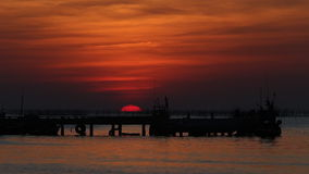 Sunset over shore of sea and fishing pier stock video footage