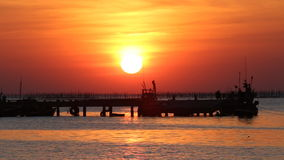 Sunset over shore of sea and fishing pier stock footage