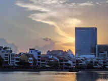 Sunset over Singapore River. Sun setting behind the tall modern building with old shop houses in the foreground stock photos