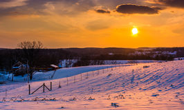 Sunset over snow-covered rolling hills and farm fields in Carrol Royalty Free Stock Photos