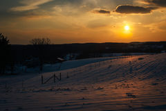 Sunset over snow-covered rolling hills and farm fields in Carrol Stock Photos