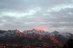 Sunset over the snow covered Santa Catalina Pusch Ridge mountains in Tucson, Arizona. Desert mountain landscape Royalty Free Stock Image