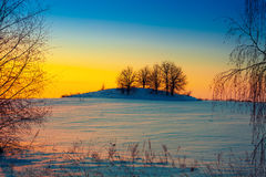 Sunset over snowy field Stock Photo