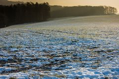 Sunset over a snowy meadow royalty free stock photography