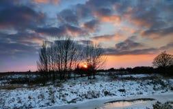 Sunset over snowy riverbank Stock Photos