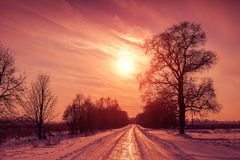 Sunset over snowy road Royalty Free Stock Photos