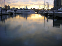 Sunset over a still marina. With boats anchores Stock Image