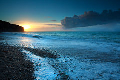 Sunset over stone beach in Atlantic ocean Stock Photography
