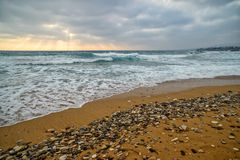 Sunset over stormy sea and empty beach Stock Images