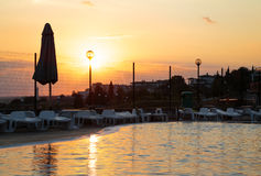 Sunset over a swiming pool at the seaside. Sunset over a swiming pool in a summer hotel at the seaside Stock Images