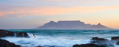 Sunset over Table Bay with Table Mountain in Cape Town. Table Mountain with breaking wave in Table Bay Royalty Free Stock Photo