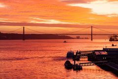 Sunset over the Tagus River. Off the Lisbon waterfront in Portugal.  In the background can be seen the Ponte 25 de Abril Stock Photos