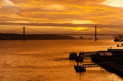 Sunset Over the Tagus River off the Lisbon Waterfront. In Portugal.  In the background can be seen the Ponte 25 de Abril Stock Photo