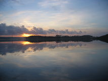 Sunset over Taksdalsvatnet. A sunset over a very still water. The water reflects the sky, making a mystic and romantic view royalty free stock photography