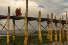 Sunset over teak bridge and walking monks. U bein bridge at sunset Amarapura ,Mandalay, Myanmar Royalty Free Stock Images
