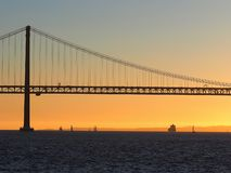 Sunset over 25th april bridge in Lisbon. Sunset over Ponte 25 de Abril bridge in Lisbon in Portugal royalty free stock photos
