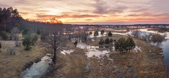 Sunset over thaw spring meadows. Streaming water at springtime. Spring melting river flood panorama. Sunset over thaw meadows. Streaming water at early Royalty Free Stock Image