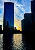 Sunset over a tower along the Chicago River as seen from the Riverwalk during winter. Sunset over the Chicago River as seen from the Riverwalk during rush hour Stock Photography