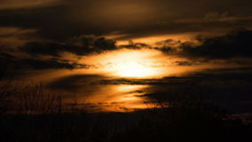 Sunset over the Trees and Clouds. Time lapse. The bright red sun moves over the horizon and the clouds and hides behind the treetops stock footage