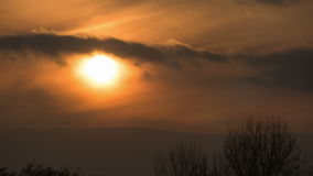 Sunset over the Trees and Clouds. Time lapse. The bright red sun moves over the horizon and the clouds and hides behind the treetops stock video footage