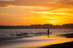 Sunset over a tropical beach with the silhouette of a boy fisherman Royalty Free Stock Photography